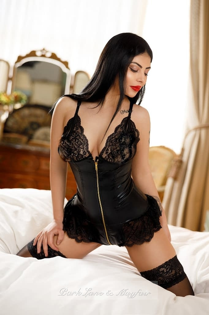 Young escort Roxy sitting on the bed in her sexy black lingerie