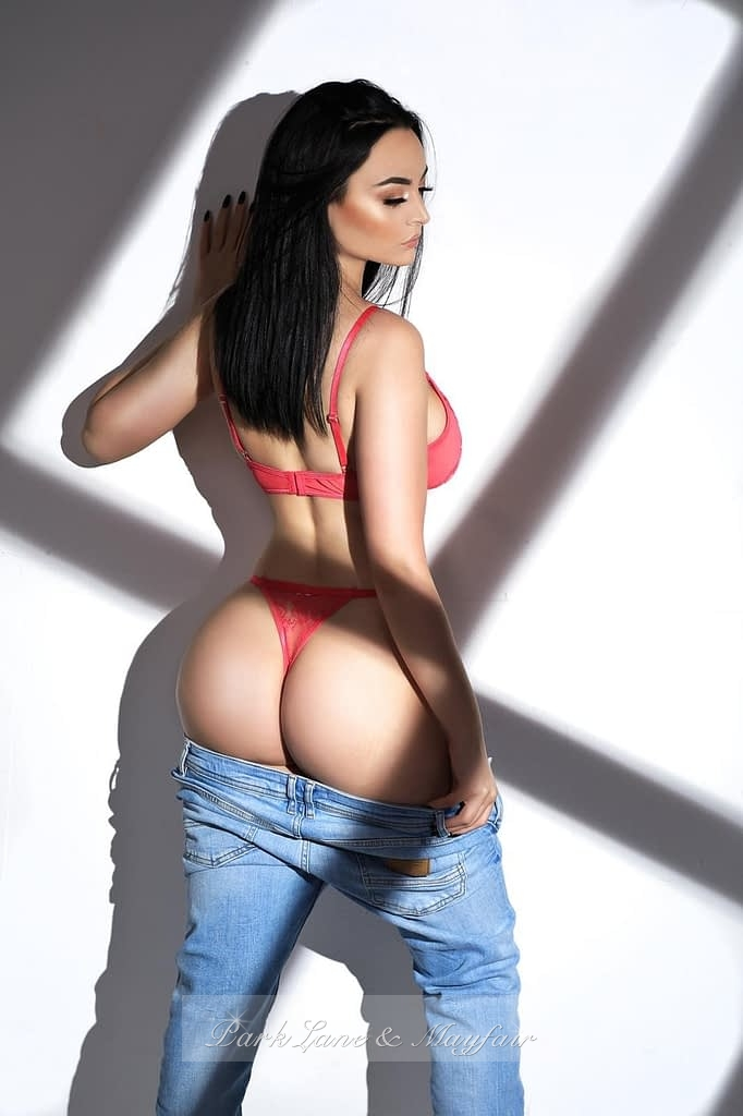 Sexy young escort Suzie standing by the wall with her jeans pulled down