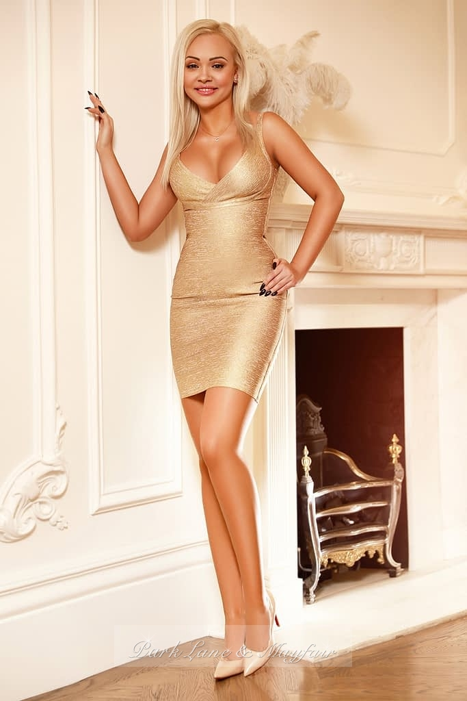 Blonde Ursula wearing a gold dress and standing by the fireplace