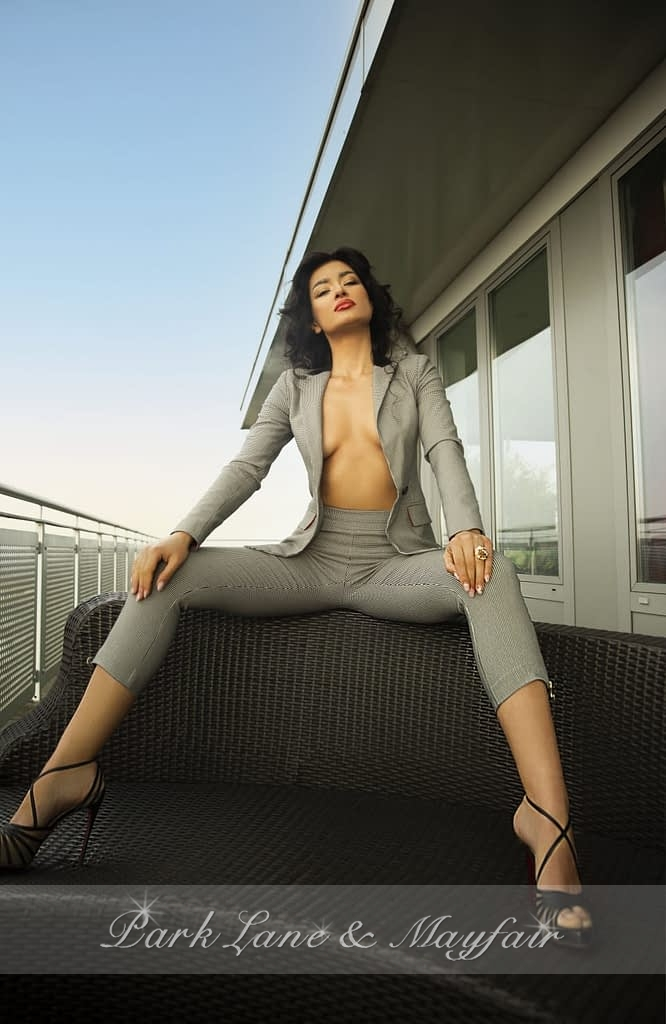 High class escort Adelyn sitting on a balcony in her suit