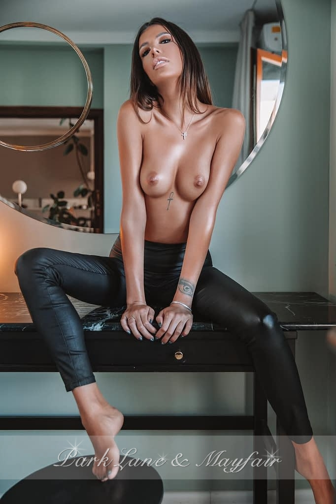 Topless escort Ivanka sitting on the table top in her leather trousers