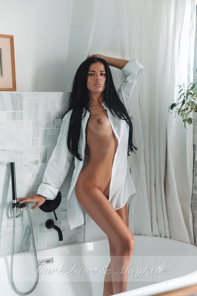 Callgirl Harper standing in the bathroom wearing just a white shirt