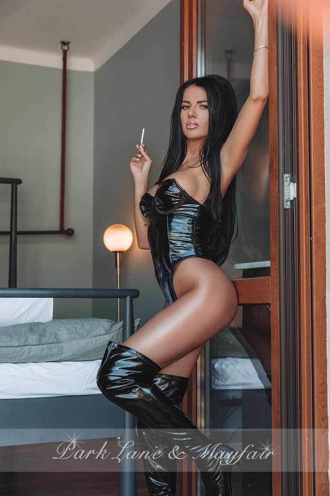 Sexy callgirl Harper standing by the bedroom door in her black leather outfit and boots