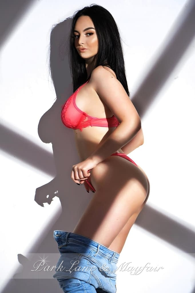 London escort Suzie posing for the camera in her pink lingerie and jeans