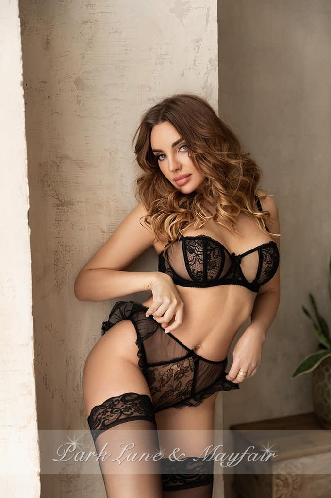 Expensive escort Ava standing by a wall in her black lingerie
