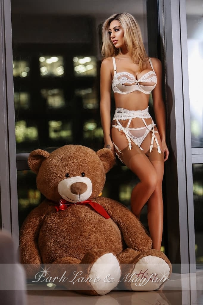 Bernice in her white lingerie standing by a large teddy