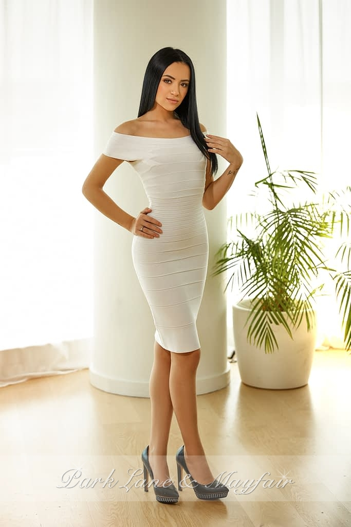 Full length photo of escort Irene dressed in her sexy white fitted dress