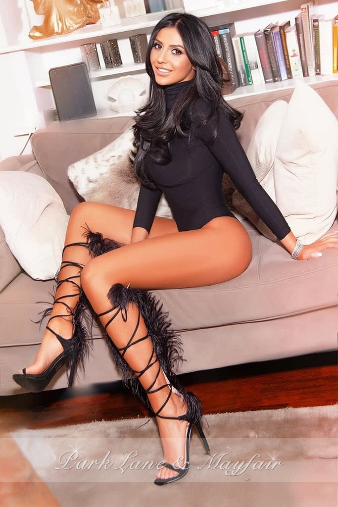 Yasmin sitting on the sofa in her black top and heels