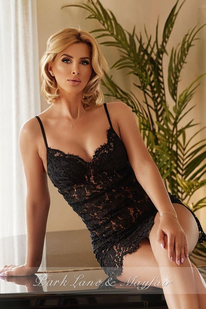 Blonde companion Annabelle sitting on a table in her black lace underwear