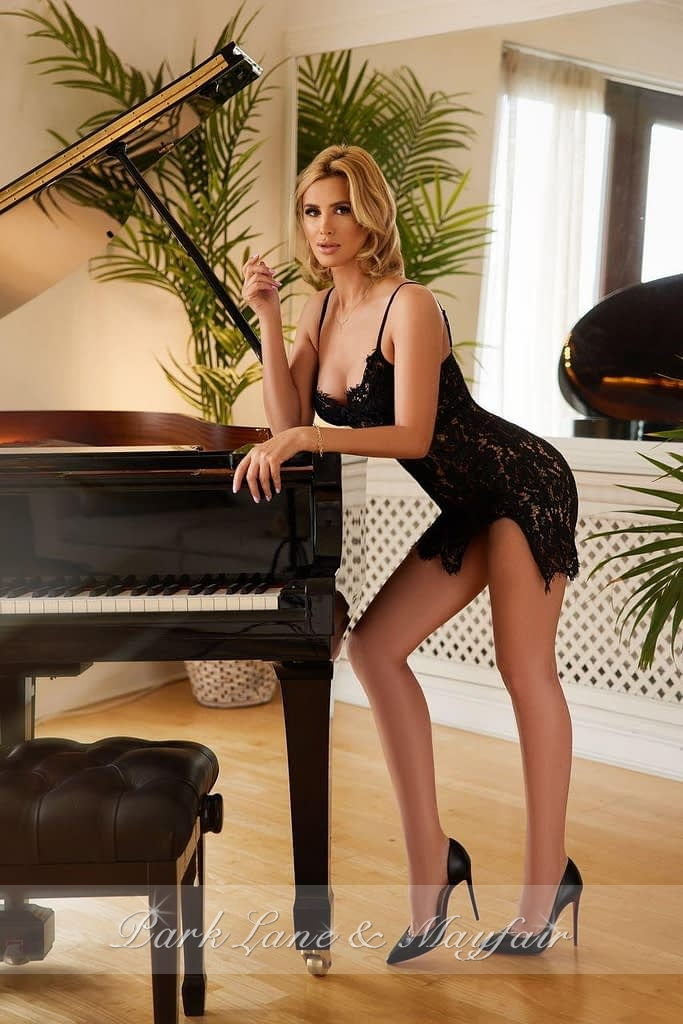 Annabelle leaning over a piano in a sexy black slip dress