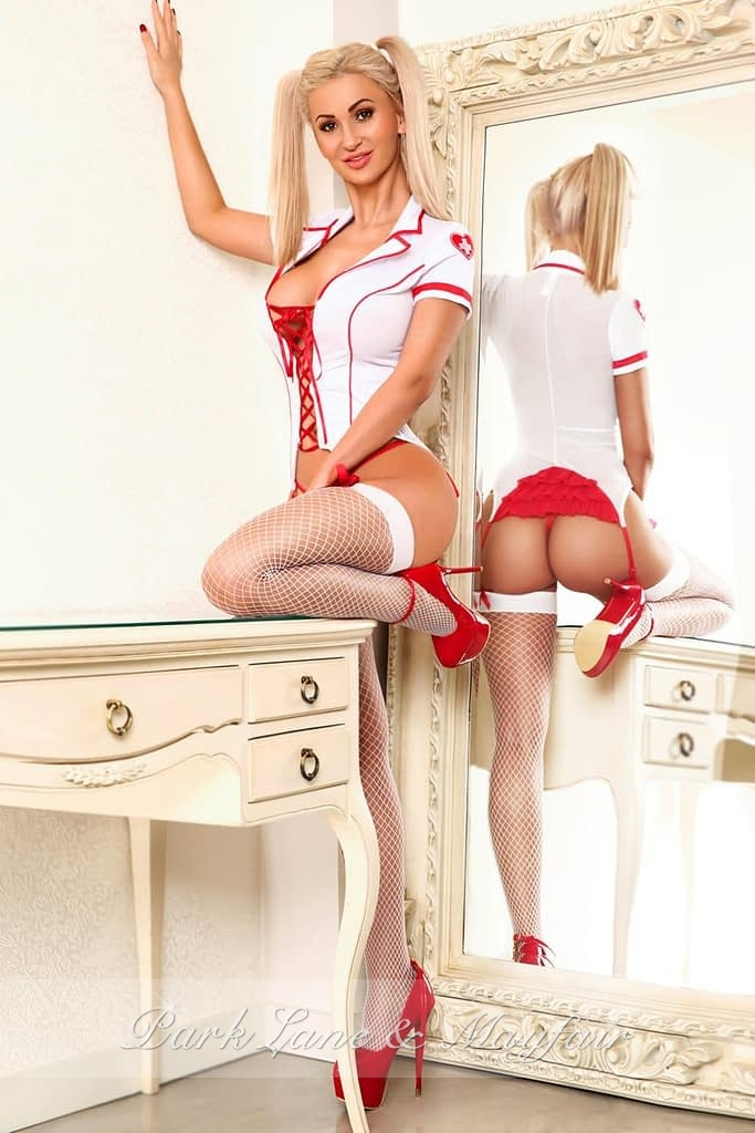 Blonde escort Chantelle standing by a large mirror in her sexy outfit