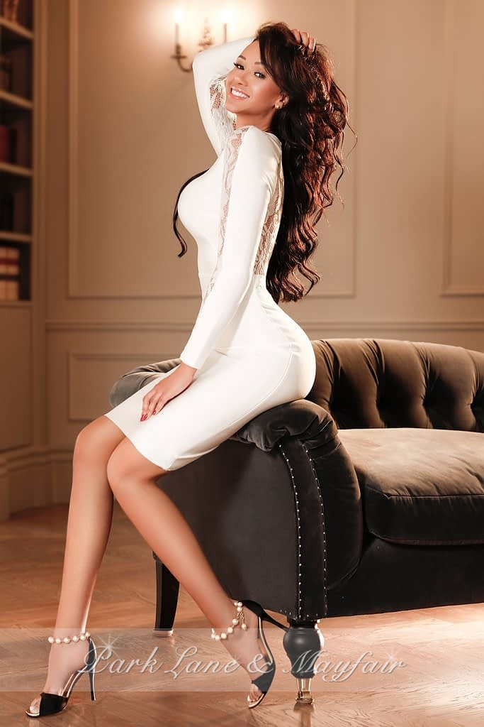 Stylish Becky sitting on a sofa arm in a sexy white dress