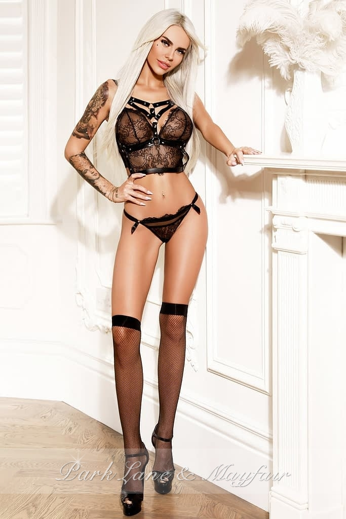 Simona standing by the fireplace in her designer black lingerie