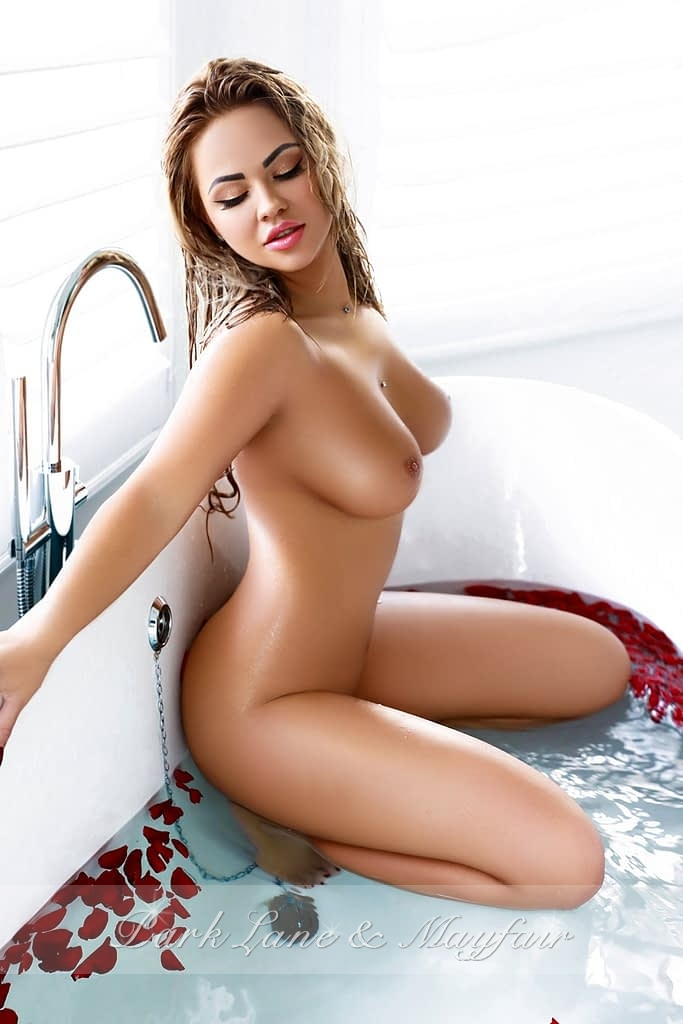 Escort Anita posing in the bath tub with red rose petals