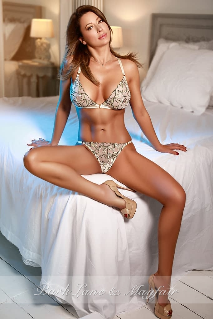 London escort Grace sitting on the bed in her lingerie