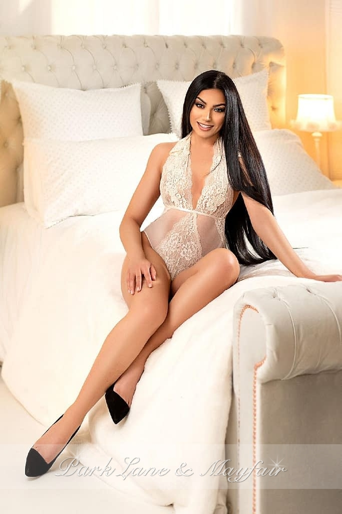 Young escort Robin sitting on the bed in her lingerie