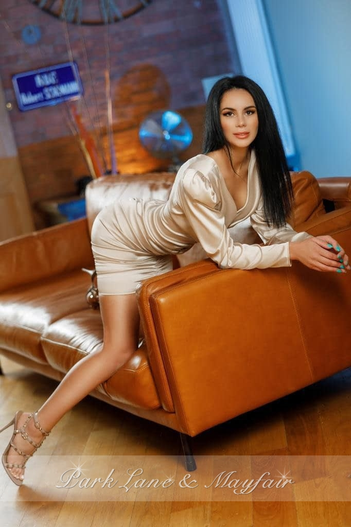 Brunette escort Ruth posing on a brown leather sofa