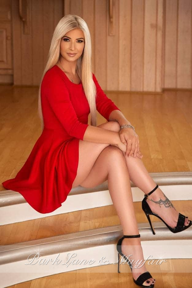 Beautiful blonde escort Summer in a sexy red dress and high heels