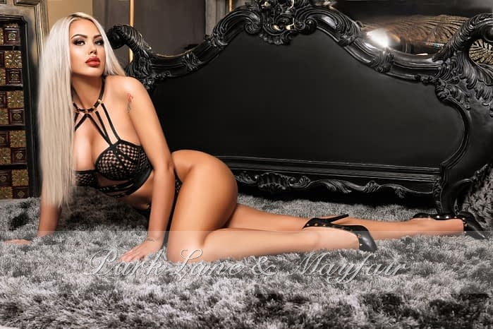 Sexy blonde Amira lying on a grey fur rug in the bedroom