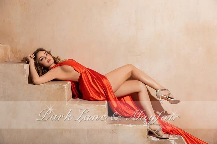 Model Ava lying on a stone staircase in an orange dress