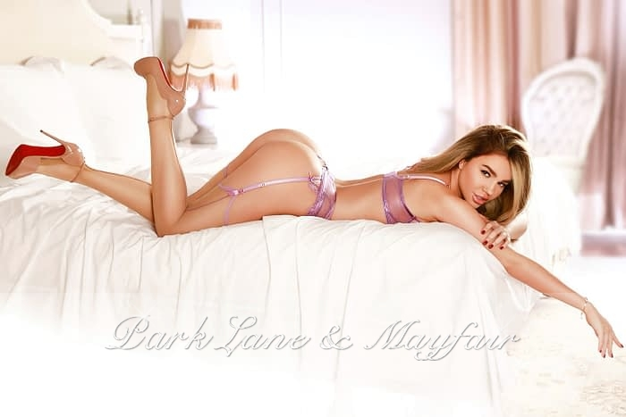 Escort Jules lying on the bed in her lingerie and heels