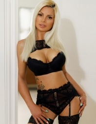 Busty blonde escort Rosetta in her black lingerie with stockings and suspenders.