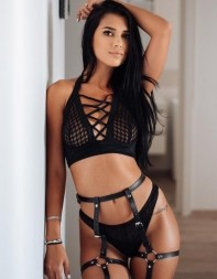 Escort Clara standing by a wall in her sexy designer lingerie