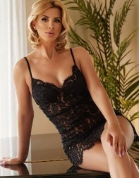 Callgirl Annabelle sitting on a tabletop in her sext black lace slip
