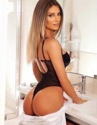 Escort Gracia in a high end hotel bathroom showing her pert bottom in the mirror