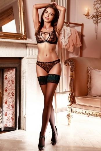 Escort in London Nicole standing in her underwear with her hands over her head