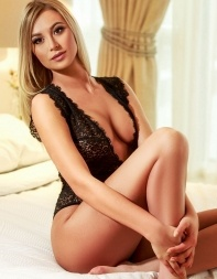 Elite escort Tabitha looking beautiful sitting on the bed.