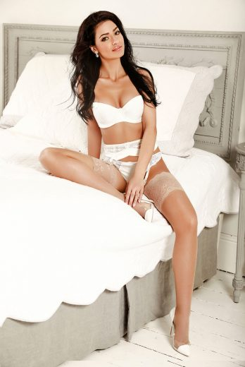 Adelyn sitting on the bed in her white lingerie