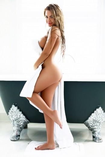 Escort Anita holding a white bath towel